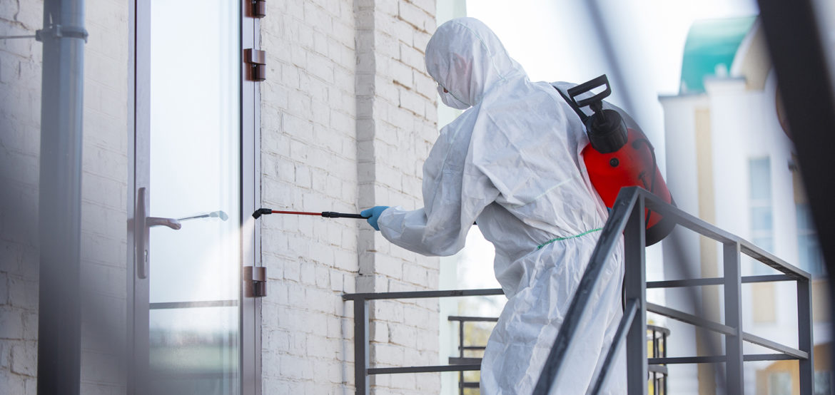 Coronavirus Pandemic. A disinfector in a protective suit and mask sprays disinfectants in the room. Protection of COVID-19 disease. Prevention of spreding pneumonia virus with surfaces we touch.