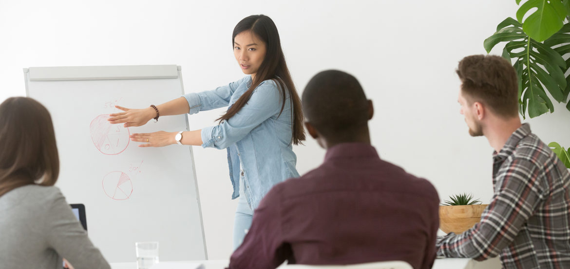 Serious asian businesswoman giving presentation to multiracial group on flipchart, japanese team leader coaching presenting corporate marketing training, explaining new plan, analyzing project result